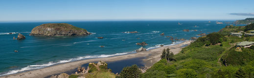 Panorama - Ocean coast line. Panorama of Harris Beach, Oregon with its sandy beach, lagoon and small rock cliff islands on a clear summer day Stock Photo