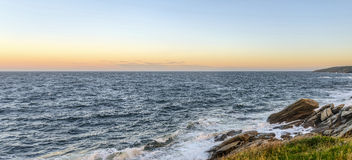 Panorama of an ocean shore at the crack of dawn Royalty Free Stock Images