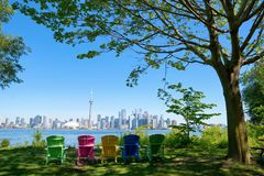 Free Panorama Of Toronto, Canada Over Chairs Different Colours And Tree From Isand On Sunny Day Royalty Free Stock Image - 122413086