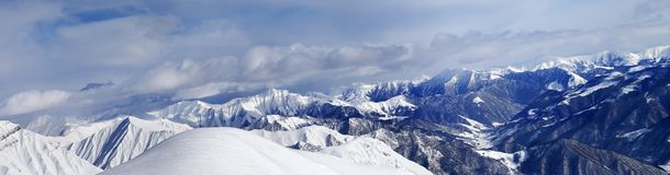 Panorama of off-piste snowy slope and cloudy mountains Royalty Free Stock Images