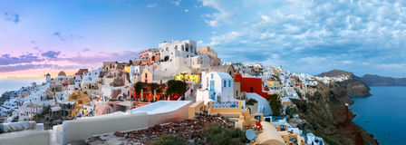 Panorama of Oia or Ia at sunset, Santorini, Greece. Picturesque panorama, Old Town of Oia or Ia on the island Santorini, white houses, windmills and church with Royalty Free Stock Photo