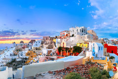 Panorama of Oia or Ia at sunset, Santorini, Greece. Picturesque panorama, Old Town of Oia or Ia on the island Santorini, white houses, windmills and church with Stock Images