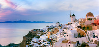 Panorama of Oia at sunset, Santorini, Greece. Panoramic famous view, Old Town of Oia or Ia on the island Santorini, white houses and windmills at sunset, Greece Stock Photo