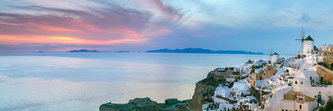 Panorama of Oia at sunset, Santorini, Greece. Panoramic famous view, Old Town of Oia or Ia on the island Santorini, white houses and windmills at sunset, Greece Stock Photography