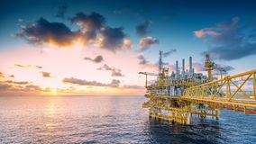 Offshore oil and gas construction platform in sun set where produced raw gases and crude for set to onshore refinery. Panorama of Oil and Gas central processing royalty free stock images