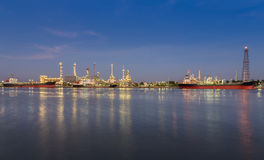 Panorama of Oil refinery at twilight along with river reflexion Royalty Free Stock Photos