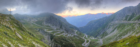 Panorama of old road St. Gotthard. Panorama of old road with tight serpentines on the southern side of the St. Gotthard pass bridging swiss alps at sunset Royalty Free Stock Image