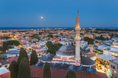 Panorama of the Old Town and the Mosque of Suleyman evening with the moon. Rhodes Island. Greece Stock Image