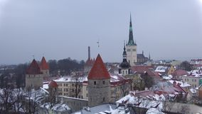 Panorama of the old town overlooking the Church of Oleviste St. Olaf in March snowfall. Tallinn, Estonia. Panorama of the old town overlooking the Church of stock footage