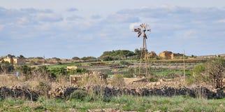 Panorama op een mooi wild het westenlandschap met steenmuren, plattelandshuisje en een gebroken windmolen in Dingli, Malta op zon royalty-vrije stock foto's