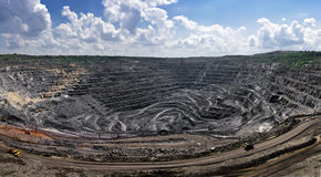 Panorama of opencast mine. Panorama of quarry extracting iron ore with heavy trucks,excavators,diggers and locomotives Royalty Free Stock Photos