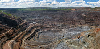 Panorama of opencast mine. Panorama of quarry extracting iron ore with heavy trucks,excavators,diggers and locomotives Royalty Free Stock Photo