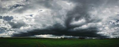 Panorama oscuro de las nubes de tormenta sobre el campo de hierba verde Foto de archivo