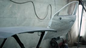 Panorama of painting chamber in an auto repair shop with car parts, hood and doors are fixing on stands