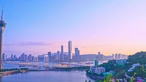 Panorama panning view of Macau Macao city skyline during sunset dusk time with Macau tower landmark and Ponte de Sai Van Bridge,