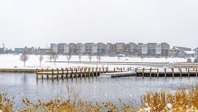 Panorama Panorama of a lake in Daybreak Utah with wooden decks and snowy shore in winter. Distant homes and buildings can be also be seen against the cloudy royalty free stock image