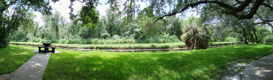 Panorama of park and lake. A panoramic view of a quiet public park with a picnic table, grassy areas, walkways and a lake in the background Stock Images