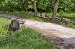 Panorama of a path with old stone bridge through a lush green summer forest Stock Photography