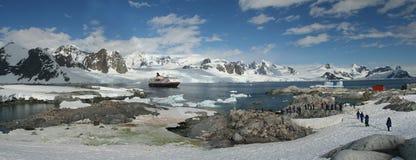 Panorama - penguin colonies, cruise ship & tourists. Petermann Island,Antarctica stock photography