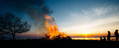 Panorama of people celebrating Walpurgis Night in Sweden. Silhouette of people by the bonfire in Walpurgis Night stock images