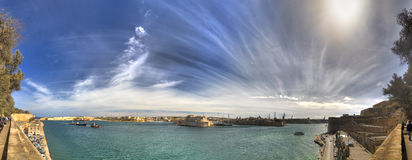 Panorama photo of the Valletta city Grand harbor area at Malta, with many historic buildings along the coastline Stock Photos