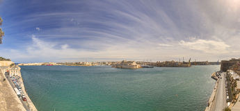 Panorama photo of the Valletta city Grand harbor area at Malta, with many historic buildings along the coastline Royalty Free Stock Photo