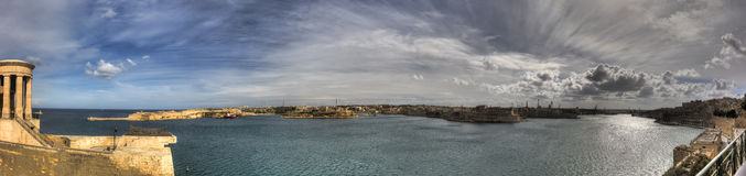 Panorama photo of the Valletta city Grand harbor area at Malta,many historic buildings along coastline and Siege Bell Memorial Royalty Free Stock Image