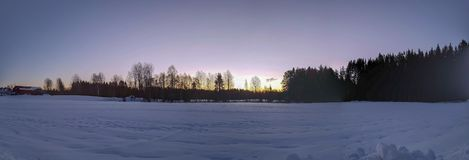 Panorama photo of winter landscape in Hedmark. Early morning photo of field and Forest landscape. Beautiful morning scene royalty free stock photo
