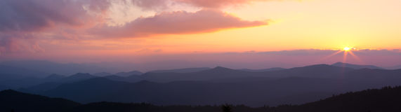 Panorama of pink sunset over mountain ridges Royalty Free Stock Photos
