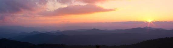 Panorama of pink sunset over mountain ridges Royalty Free Stock Photos