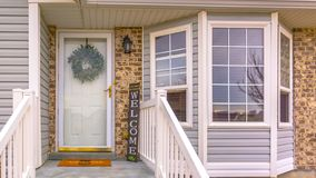 Panorama Pleasing home with stairs and half hexagon shaped window at the facade. A wreath, doormat, welcome sign, and wall lamp adorn the doorway royalty free stock photo