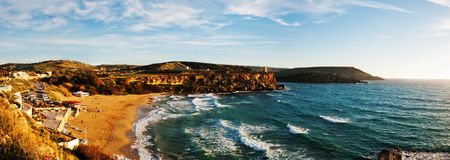 Panorama: Golden Sands Bay Malta. Panorama of the popular sandy beach of Golden Sand Bay, Malta awash in evening sunlight Stock Photos