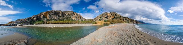 Panorama of Preveli beach at Libyan sea, river and palm forest, southern Crete. Royalty Free Stock Photography