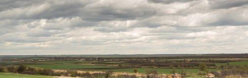 Panorama Primavera Paisaje rural con las nubes grises sobre los campos y el pueblo Fotografía de archivo libre de regalías