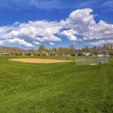 Panorama quadrado de um campo de futebol com casas e da montanha na distância fotos de stock royalty free
