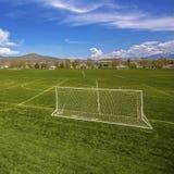 Panorama quadrado do quadro de um campo de futebol com casas e da montanha na distância imagens de stock royalty free