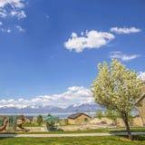 Panorama quadrado do quadro do parque e das casas com vista do lago e da montanha sob o céu nebuloso fotos de stock