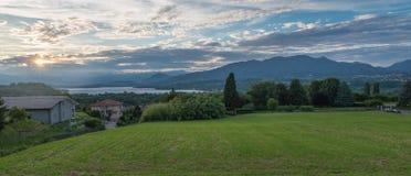 Panorama que sorprende con las montañas y el lago en la puesta del sol Lago Italia varese foto de archivo