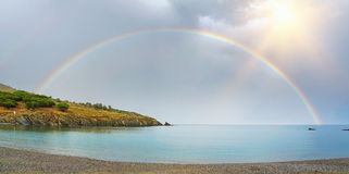 Panorama of a rainbow half over sea and land. Panorama of a rainbow, half over sea and land viewed from the pebble beach of Bernardi in the Mediterranean bay of Stock Image