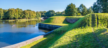 Panorama of rampart of Naarden, Netherlands. Bastion Oranje and people in boat cruising on moat of old fortified town of Naarden, North Holland, Netherlands Royalty Free Stock Images