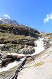 Panorama rapido della corrente, del ponte e della montagna, alpi di Hohe Tauern, Austria Immagini Stock Libere da Diritti