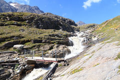 Panorama rapido della corrente, del ponte e della montagna, alpi di Hohe Tauern, Austria Fotografia Stock