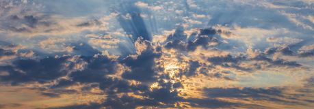 Panorama rays of the sun dramatic clouds. Background panorama. rays of the sun make their way through dramatic clouds Royalty Free Stock Photo