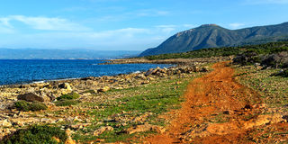 Panorama. Red dirt road on the beach. Cyprus. Stock Photos
