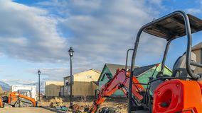 Panorama Red excavator on a construction site for new homes against cloudy blue sky royalty free stock photo