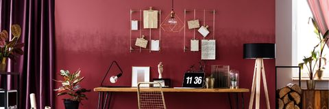 Panorama of red workspace interior. With gold clock and poster on wooden desk near plant at window Royalty Free Stock Photography
