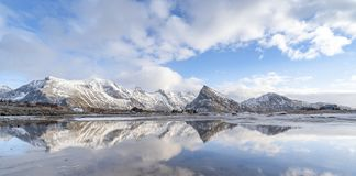 Panorama reflection of snowy mountains, blue sky and clouds on the calm clear water on a beach. A range of pointy mountain in beautiful winter landscape of stock photo