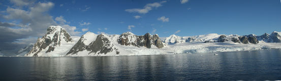 Panorama - Reflections Of Glacial Icefalls And Mountains, With Cloudy Blue Sky Stock Photography