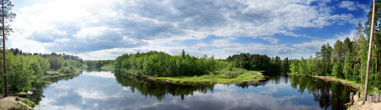Panorama of a river flowing through a forest. Royalty Free Stock Image