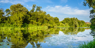 Panorama with river. Summer warm evening. Panorama with river views from the footbridge. The village is in the background. Reflection of blue sky in the river Royalty Free Stock Photos